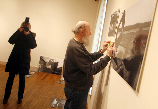 Gloucester: Paul Miller hangs photos of former Gloucester Times photogrpaher Charlie Lowe at the Cape Ann Museum as Gloucester Times photographer Mary Muckenhoupt documents the process.  The exhibit opens March 7. Mary Muckenhoupt/Gloucester Daily Times