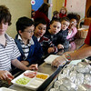 "Gloucester: Tony Petrilli makes a face as Maureen Foster sets out trays of green eggs and ham during lunch at West Parish Elementary School yesterday afternoon. The school created a special menu to commemorate the birthday of children's author Dr. Seuss, who wrote ""Green Eggs and Ham."" Petrilli and his classmates (from left) Brendan O'Brien, AJ Romeo, CJ Renales, Isaiah Smith, and Carissa Snow, could be adventurous and eat the special meal or opt for spaghetti or cheeseburgers. Photo by Kate Glass/Gloucester Daily Times Tuesday, March 3, 2009"