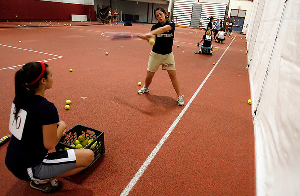 Gloucester: Samantha Saputo focuses on her swing as Ashley Lopes prepares to toss her another ball during the first day of softball practice yesterday. Photo by Kate Glass/Gloucester Daily Times Monday, March 16, 2009