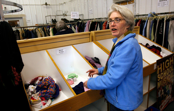 Gloucester: Anne Strong, manager of the Second Glance Resale Shop, points to bins that used to be overflowing with clothing. The shop had to get rid of all clothing with metal parts such as zippers and buttons because a new law holds them responsible if the items contain lead. Photo by Kate Glass/Gloucester Daily Times Tuesday, March 10, 2009