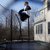 Manchester: Charlie Baker, 10, jumps on the trampoline outside his home on Tuesday afternoon. He says his favorite trick is a front flip 180. Photo by Kate Glass/Gloucester Daily Times Tuesday, March 17, 2009