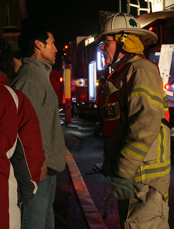 Gloucester: Gloucester Fire Chief Phil Dench speaks with the son of the owner of 13 Commonwealth Ave. as they extinguish a blaze in the building last night. Photo by Kate Glass/Gloucester Daily Times