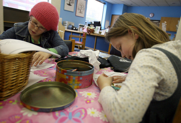 Gloucester: Olivia Peavey, left, and Emily Grace, both 7, focus on their coloring projects at the Sawyer Free Library yesterday afternoon. Photo by Kate Glass/Gloucester Daily Times