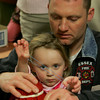 Essex: Annaleigh Akerly, 2, stretches out a rubber band while making a drum with her dad, Ed, at Noisy Music Night at the Essex Elementary School Friday night. Mary Muckenhoupt/Gloucester Daily Times