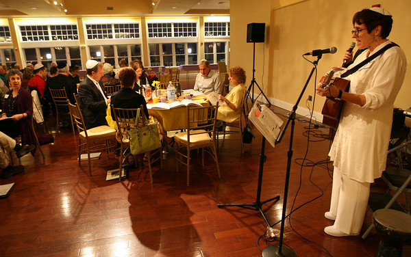 Gloucester: Shoshana Brown leads members of Temple Ahavat Achim in song during a Community Seder at Cruiseport last night. Photo by Kate Glass/Gloucester Daily Times