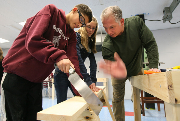 Gloucester: Stephen Sacca, right, an MIT alumnus of East Gloucester, helps Brian Matos and Kirsten Salo, both eighth grade students at O'Maley Middle School, cut pieces of wood to make an Eastern Bluebird Nestbox yesterday. All eighth graders will make nest boxes through the project, which focuses on how to use tools so they can apply that knowledge to study manufacturing. The project is sponsored by the Gloucester Education Foundation's Sea Initiative, a collaboration between the Gloucester Public Schools and MIT. Photo by Kate Glass/Gloucester Daily Times
