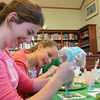 Manchester: Devon Musgrave-Johnson, 13, decorates her shamrock cookie as her friend Lauren Coogan, 12, watches during cookie decorating with Deb Kaneb at the Manchester Public Library Wednesday afternoon. Devon was being very creative with her cookie decorations which included a beach scene made of frosting. Also pictured is Kristen Kaneb, right. Mary Muckenhoupt/Gloucester Daily Times