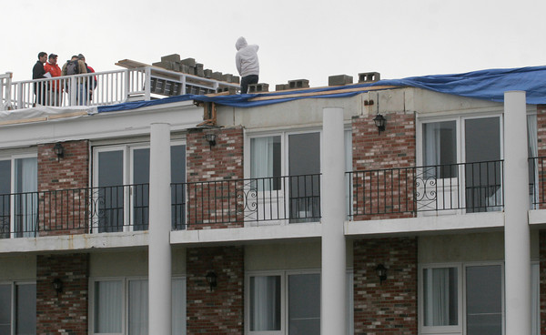 Gloucester: Workers begin to repair the roof of the Bass Rocks Ocean Inn on the Back Shore yesterday. Portions of the roof had blown off in the storm Thursday night. Photo by Kate Glass/Gloucester Daily Times