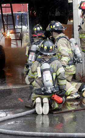 Gloucester: Gloucester Firefighters Tony Trupiano, Mike Chipperini, and Bruce Wonson hose down the area surrounding a small fire at Rose's Marine yesterday afternoon. A gas tank in one of their buildings ignited, but did not appear to cause much damage. Photo by Kate Glass/Gloucester Daily Times