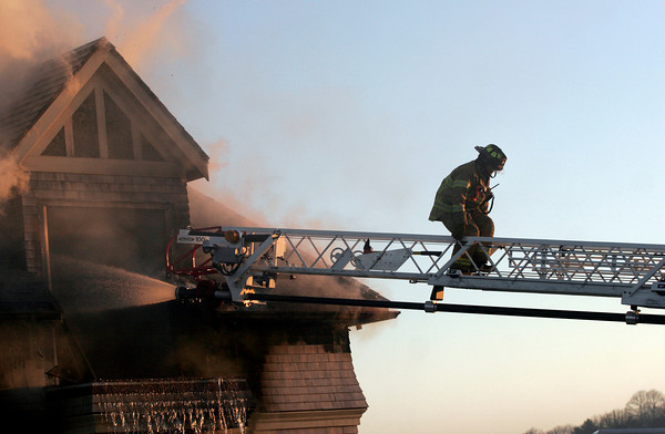 Gloucester: A Gloucester Firefighter climbs down the ladder as they battle a blaze on Bass Rocks Road yesterday evening. Photo by Kate Glass/Gloucester Daily Times
