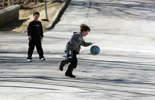 Gloucester: Jake Engel, 6, dribbles the ball while playing basketball with his friend Jameson Kamm, 11, on Pleasant Street Saturday morning. Mary Muckenhoupt/Gloucester Daily Times