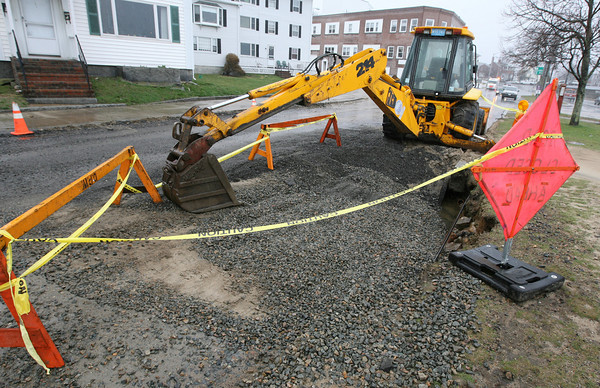 Gloucester: A backhoe is roped off near the site of a water main break on Western Avenue yesterday. The main broke early Tuesday morning, disrupting water service to the area. Photo by Kate Glass/Gloucester Daily Times