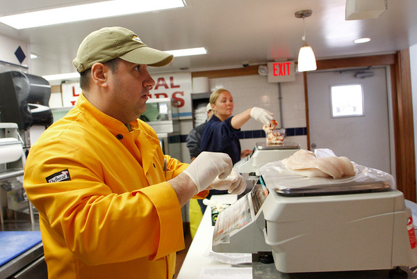Gloucester: Jeff DiMeo weighs some haddock for a customer at Intershell Friday afternoon. Mary Muckenhoupt/Gloucester Daily Times