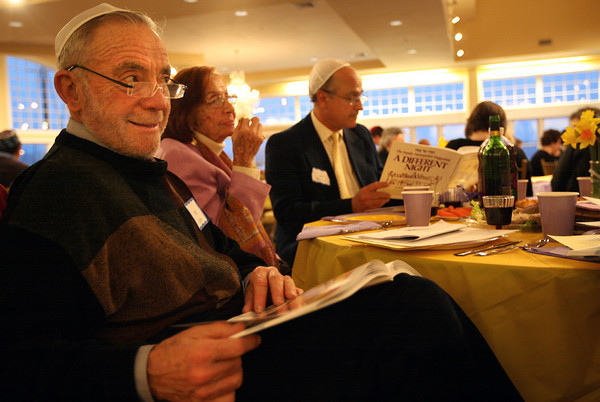 Gloucester: Phil Cutter looks through the Haggadah during Temple Ahavat Achim's Community Seder at Cruiseport last night. Photo by Kate Glass/Gloucester Daily Times