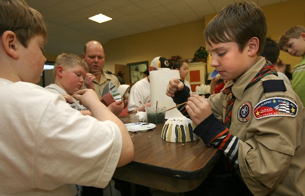 Rockport: Ben Fuller, 10, right, focuses on the finishing touches of his bowl as he and fellow members of Rockport Cub Scout Pack 55 paint bowls at Open Door for their annual Empty Bowl Dinner yesterday afternoon. Rockport girl scouts also participated in the event. Photo by Kate Glass/Gloucester Daily Times
