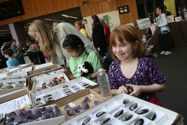 Gloucester: Katie Ryan, 7, of Gloucester is happy with her decision to buy an othoceras fossil from the crystal, mineral, and fossil table at O'Maley Middle School's Spring Fling Fair Saturday afternoon.  Proceeds from this table went to fund teacher grants however some proceeds from the fair helped to raise money to equip and modify a wheelchair van for Cherylann Parker, longtime Gloucester educator who was injured in a horseback riding incident last fall. Mary Muckenhoupt/Gloucester Daily Times