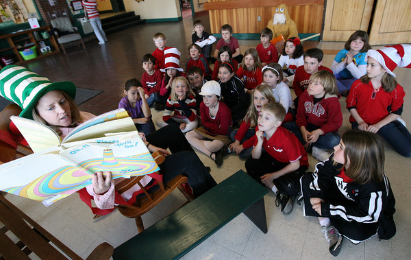 """Manchester: Susan Gould reads """"Oh the Places You'll Go!"""" to her second grade class in the lobby of Manchester Memorial Elementary School yesterday afternoon as the school celebrates Dr. Seuss' birthday. Photo by Kate Glass/Gloucester Daily Times"""