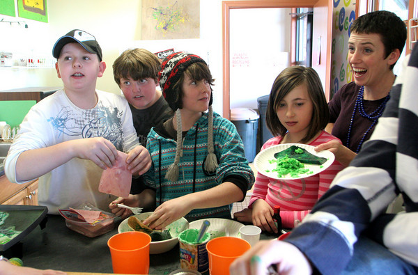 Rockport: Nikki Klink, teen director at the YMCA Ben Beyea Youth and Teen Center, hands out some green eggs and ham to celebrate St. Patrick's Day as Austin Chambers, 12, Paul Zopatti, 11, Charlie Larsen, 12, and Kailee Ruphard, 11, work in the kitchen at the teen Center in Rockport Wednesday afternoon.  The kids said that although green eggs and ham doesn't look appetizing it tastes good. Mary Muckenhoupt/Gloucester Daily Times