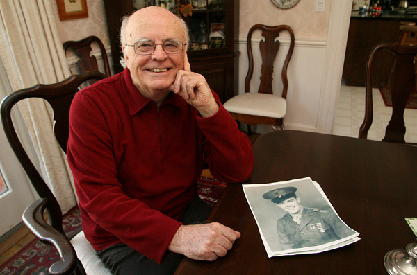 """Manchester: Iwo Jima veteran Larry Kirby of Manchetser was interested to see the HBO series """"The Pacific"""" and has viewed the first episode of the 10 part miniseries. Here Larry sits in his Summer Street home in front of a photo of him taken when he joined the service nealry 70 years ago. Mary Muckenhoupt/Gloucester Daily Times"""