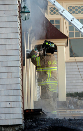 Gloucester: Gloucester Firefighter William Doucette cuts through garage doors as they extinguish a fire on Bass Rocks Road yesterday evening. Photo by Kate Glass/Gloucester Daily Times