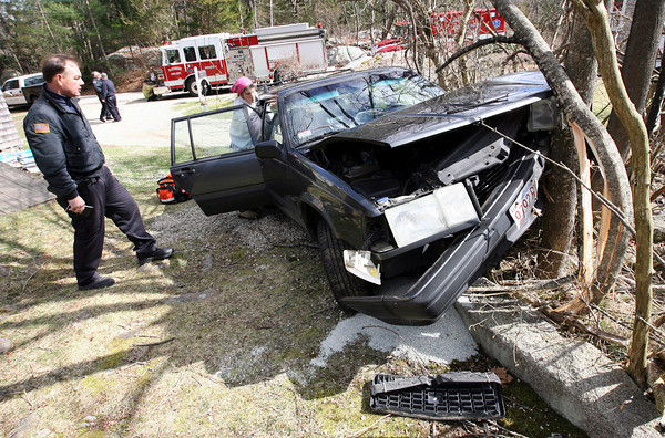 Gloucester: Gloucester Police Officer Bill Cahill surveys the damage after a woman drove her car into a tree on Bray Street yesterday afternoon. She sustained minor injuries in the accident. Photo by Kate Glass/Gloucester Daily Times