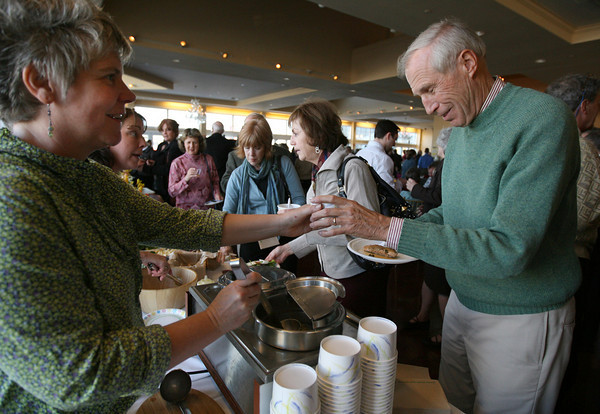 Gloucester: Kate Noonan of Common Crow hands Cameron Smith of Rockport a sample of their chowder during the Taste of Cape Ann event at Cruiseport last night. Photo by Kate Glass/Gloucester Daily Times