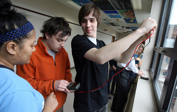 Rockport: Robin Lovell holds a dye-sensitized solar cell up to the light so Ethan Finlan can measure the voltage as Raks Derival of Beyond Benign looks on at Rockport High School yesterday morning. The program, which focuses on green chemistry technology, hopes to inspire students to pursue a career in science by showing practical applications. Photo by Kate Glass/Gloucester Daily Times