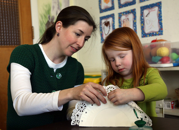 Rockport: Molly Whelski helps Kaelan Mulkern make an Irish lace fan at Sandy Bay Preschol as they celebrate St. Patrick's Day yesterday. Photo by Kate Glass/Gloucester Daily Times