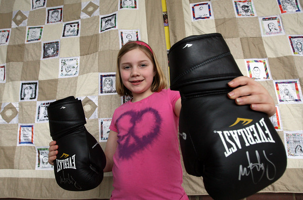 Gloucester: Brooke Cleary, a student at West Parish Elementary School, holds up a pair of boxing gloves signed by actor Mark Wahlberg, which will be up for auction at Cruising for Education tonight at 6 at Cruiseport. Proceeds from the auction benefit West Parish Elementary School. Photo by Kate Glass/Gloucester Daily Times