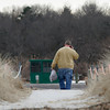 Gloucester: A man carries a bag of disks from the Hooksett, N.H. wastewater treatment plant that washed ashore at Wingaersheek Beach yesterday following an overflow at the plant. The man would not identify himself or what agency he was with, but did confirm that the disks were from the Hooksett plant. Photo by Kate Glass/Gloucester Daily Times