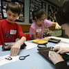 "Gloucester: Aiden Cunha writes the name of his squid, ""Ben,"" using squid ink while dissecting the animal during ""March Madness: Science with Lisa"" at the Sawyer Free Library yesterday. Next to Aiden are Andraya Ortiz and Benjamin Smith. Photo by Kate Glass/Gloucester Daily Times"
