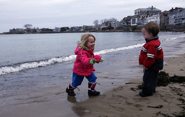 Rockport: Lizzie Sly, 3, runs toward her brother, Alex Sly, almost 2, to avoid the rising water at Front Beach yesterday afternoon. Photo by Kate Glass/Gloucester Daily Times