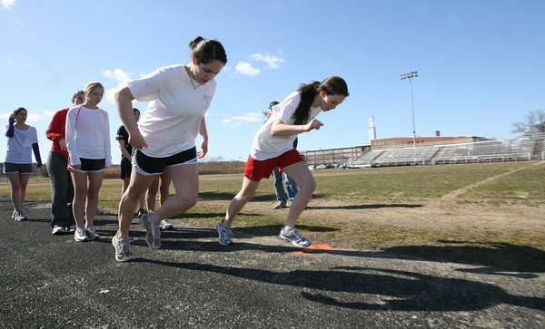 Gloucester: Captain Ellie Cornavaca and Tori Hilshey lead the girls track team in warmups during practice yesterday. Photo by Kate Glass/Gloucester Daily Times