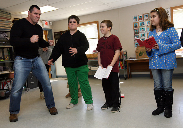 "Gloucester: Fitness trainer Bo Cleary helps Jett Sayess with his stance to show he's the ""strong prince"" during a rehearsal for the Beeman Elementary School's production of ""Doo Wop Wed Widing Hood"" as castmates Ben Oliver and Rosie Giambanco look on. Cleary also taught the students some stretches and relaxation techniques to do before the show, which will be performed April 6-7. Photo by Kate Glass/Gloucester Daily Times"