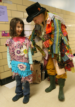 """Gloucester: Sabrina Zemlyasky, a first grade student at West Parish Elementary School, giggles as Lara Lepionka helps her put on a costume so she can take part in the performance of """"Stone Soup"""" on Thursday. The performance, which is based on the story by author Marcia Brown, teaches the imprtance of community. Photo by Kate Glass/Gloucester Daily Times"""