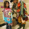 "Gloucester: Sabrina Zemlyasky, a first grade student at West Parish Elementary School, giggles as Lara Lepionka helps her put on a costume so she can take part in the performance of ""Stone Soup"" on Thursday. The performance, which is based on the story by author Marcia Brown, teaches the imprtance of community. Photo by Kate Glass/Gloucester Daily Times"