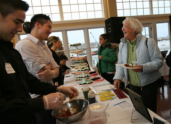 Gloucester: Virginia Ekborg of Gloucester chats with Shane O'Neill, left, and Quinn O'Neill from the Franklin Cafe as she tries their tuna tartare at the Taste of Cape Ann at Cruiseport yesterday. Proceeds from the event, which is sponsored by the Gloucester Daily Times and Cape Ann Magazine, benefit the Open Door and Cape Ann Animal Aid. Photo by Kate Glass/Gloucester Daily Times