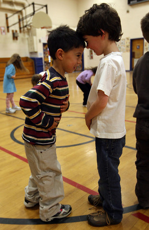 Essex: Zachary Lee, left, and Brady Friedrich jokingly butt heads as they bow to each other while working on a dance during gym class at Essex Elementary School last week. Photo by Kate Glass/Gloucester Daily Times