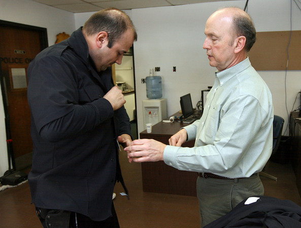 Gloucester: Sgt. Michael Gossom tries on one of the Gloucester Police Department's new uniforms yesterday as Tom Simonelli of Flying Cross checks the size. Photo by Kate Glass/Gloucester Daily Times