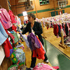Manchester: Jennifer Ware of Essex hangs a display of rain jackets that will be for sale at the Children's Drop & Shop at Brookwood School in Manchester yesterday afternoon. Photo by Kate Glass/Gloucester Daily Times