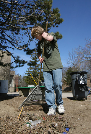 Gloucester: Jebediah Hogan rakes up debris in front of O'Maley Middle School during a spring cleanup yesterday afternoon. The seventh grader, who is a member of the track team, will receive a discount on his sports user fee for his work. Photo by Kate Glass/Gloucester Daily Times