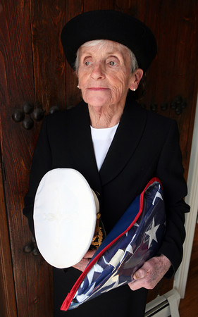 Jennifer McCarthy holds the hat and American flag of her husband,  Marine Corps Col. Donald Joseph McCarthy at their Rockport home. He was buried at Arlington National Cemetery recently. AMY SWEENEY/Gloucester Daily Times.