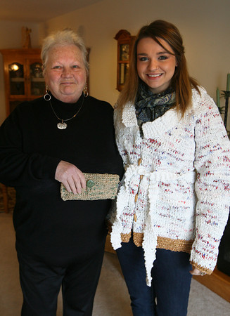 Gloucester: Donna Wright holds a wallet her granddaughter, Shaina Stowell, knit from recycled shopping bags as Shaina models a coat knit from the same material by Donna. Photo by Kate Glass/Gloucester Daily Times