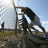 Gloucester: Phil Curcuru holds onto the fence at Newell Stadium while working out with the track team yesterday afternoon. Photo by Kate Glass/Gloucester Daily Times
