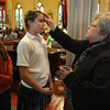 Gloucester: Sister Judy O'Brien, Principal of St. Ann School, makes a cross in ashes on the forehead of eighth grade student Grace Papp as classmate Claudia Torres looks on during an Ash Wednesday service at St. Ann Church yesterday afternoon. Ash Wednesday is the first day of Lent, the season leading up to Easter. Photo by Kate Glass/Gloucester Daily Times