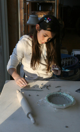Rockport: Light from the setting sun falls on Mickey Coonley as she works on a bowl at Cynthia Curtis Pottery. The bowl is constructed of tiny discs of clay instead of being shaped from a large piece. Photo by Kate Glass/Gloucester Daily Times