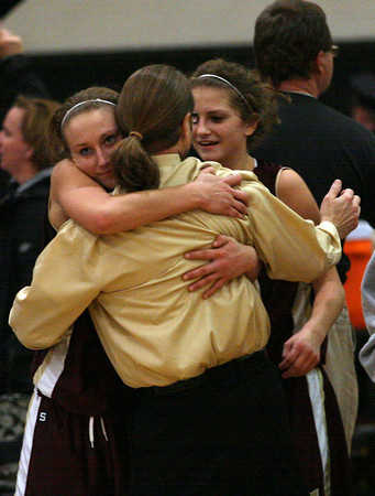 Hannah Cain and her sister, Heather Cain hug head coach Jon Flanagan as they celebrate their 66-62 win over Reading during the MIAA Division 2 North Semi-Finals at Woburn High School last night. Photo by Kate Glass/Gloucester Daily Times