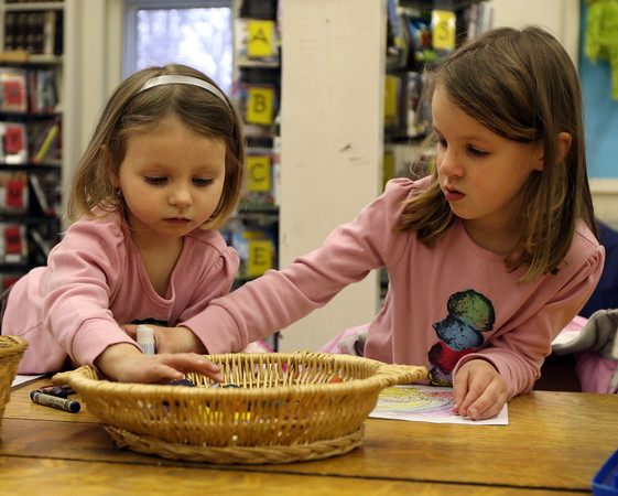 Essex: Evelyn Durrey and her sister, Grace, share crayons and glue as they work on an art project at the TOHP Burnham Library following Story Hour on Wednesday. Photo by Kate Glass/Gloucester Daily Times