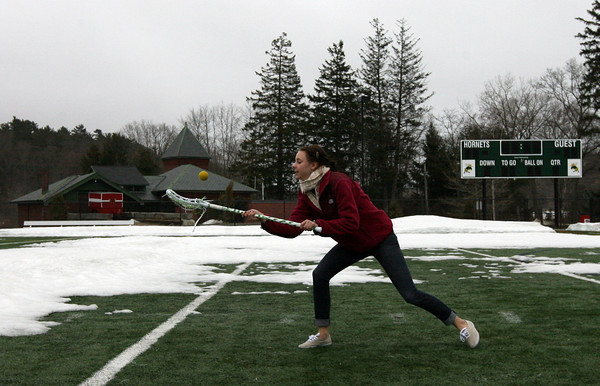 Manchester: Chrissy Pries, a sophomore at Manchester Essex Regional High School, practices using a lacrosse stick with friends Maddi Bistrong and Ella Stearns (not shown) at Hyland Field on Thursday. Pries is hoping to try out for the lacrosse team when the season begins next Monday. Photo by Kate Glass/Gloucester Daily Times