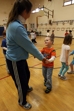 Essex: Jack Crompton, a kindergarten student at Essex Elementary School, looks up to physical education teacher Linda Collins as they practice a dance from Germany during class on Thursday. The kids have been learning about cultures from around the world this month, including foods they eat and traditional dances. Jack got to dance with the Ms. Collins because it was his birthday. Photo by Kate Glass/Gloucester Daily Times